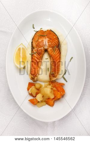 fried scottish salmon steak with mashed potatoes and honey glazed root vegetables on oval plate