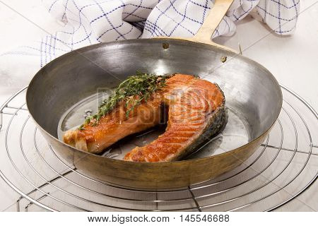 fresh fried scottish salmon steak and thyme in a brass pan