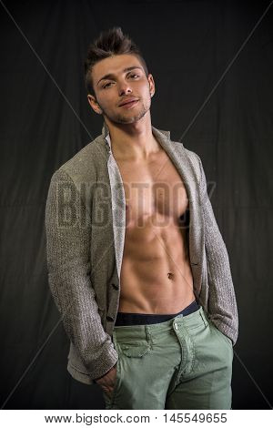 Confident, attractive young man with open jacket on muscular torso, ripped abs and pecs. Side view