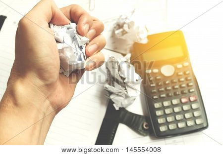 Businessman sitting at desk in a little office or home mad at work ripping documents with frustrated hand expression. Throwing around scraps of paper. Negative human emotions soft focus