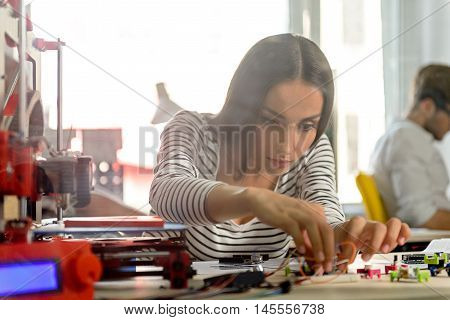 Professional female engineer is constructing 3d printer with concentration. She is sitting at desk in office