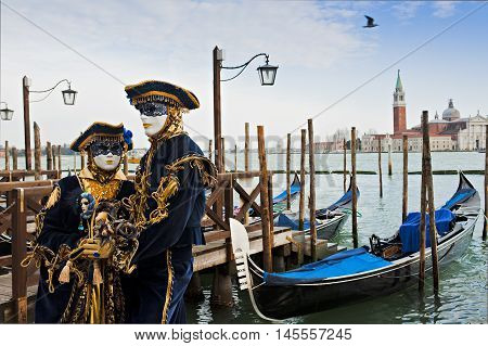 A laddy with gentleman in carnival mask in Venice. In the background the church of Saint George.