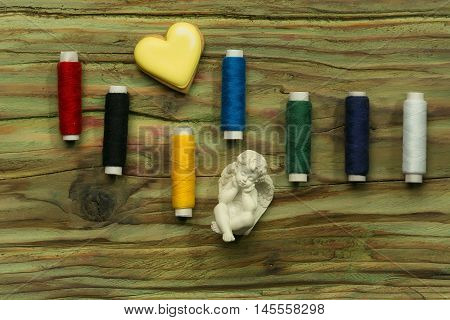 Set of bobbins of sewing colorful stitch for handwork cookie in heart shape and figure of angel on wooden background