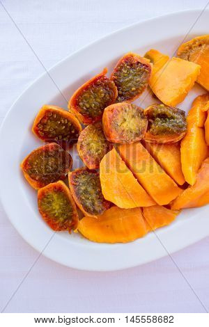 Prickly pear cactus fruits and mango fruits cutted in pieces on the white plate and background. Salad of mango and prickly pear cactus fruits in a white plate. Vertical. Close. Top view.