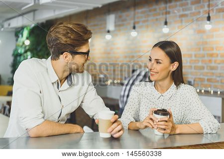 Happy young couple is dating in cafe. They are drinking coffee and talking. Man and woman are smiling