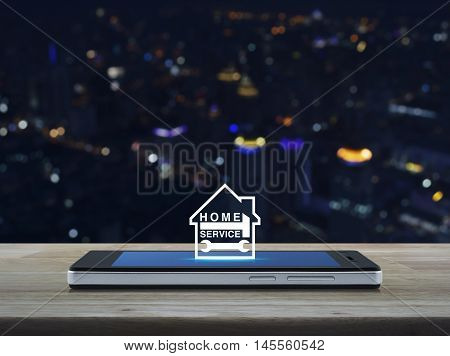 Hammer and wrench with house icon on modern smart phone screen on wooden table in front of blurred light city tower Home service concept
