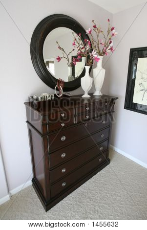 A dresser with flowers inside a home interior poster