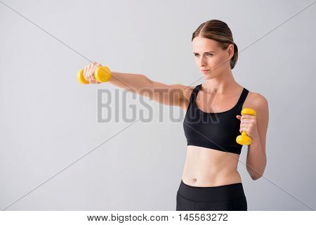 Sport fun. Content and cheerful young woman using dumb bells while standing on isolated grey background