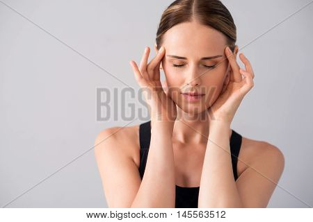 Unbearable. Cropped image of sad and depressed young woman having headache being on isolated grey background