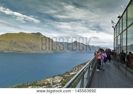 Queenstown, New Zealand - March 2016: Tourists At The Terrace Overlooking View Of Lake Wakatipu And