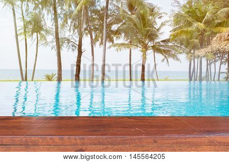 Empty Wooden table on swimming pool with sea background.