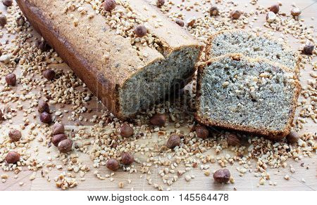 German homemade hazelnut loaf cake on wooden board surrounded by whole and chopped hazelnuts. Whole cake decorated with hazelnuts and 2 slices cut off.
