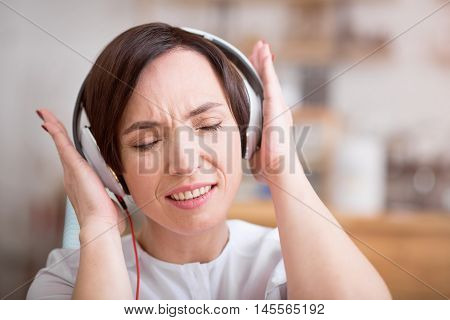 Music therapy. Close-up portrait of delighted young woman listening music using headphones with shut eyes