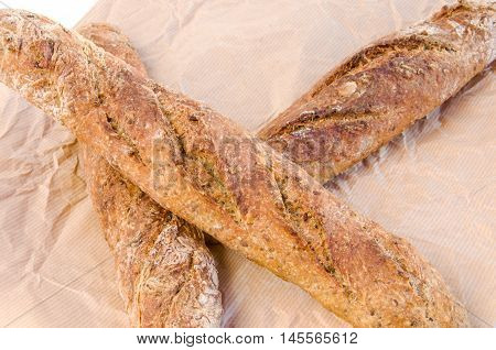 Three fresh home baked Alpine Baguettes with different cereals and seeds on paper sheet. Healthy food concept. Close-up.
