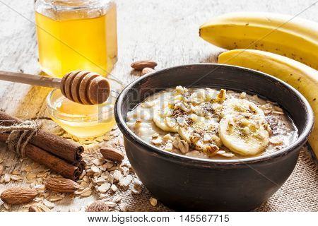 oatmeal porridge in dark ceramic bowl. with honey, banana, cinnamon and nuts. healthy breakfast. close up