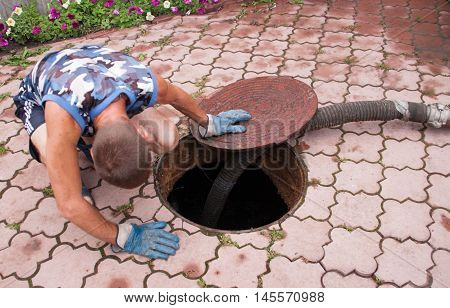 man pumping sewage from the hole in the summer