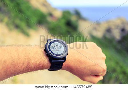 Runner or hiker on mountain trail looking at sports watch healthy lifestyle. Checking GPS position performance or heart rate pulse and training working out. Sport and fitness outdoors in nature.