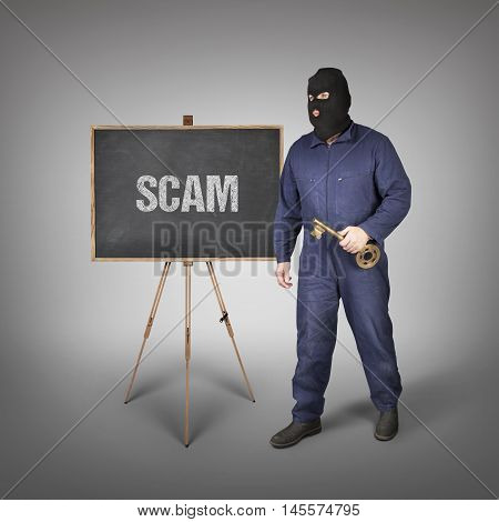 Scam text on blackboard with thief and key