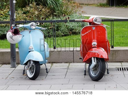 STOCKHOLM SWEDEN - SEPTEMBER 03 2016: One blue and one red retro vespa scooters parked before the start of the Mods vs Rockers event at the Saint Eriks bridge Stockholm Sweden September 03 2016