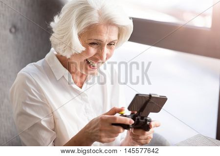 Like doing it. Overjoyed delighted senior woman sitting at the table and holding game console while playing video games