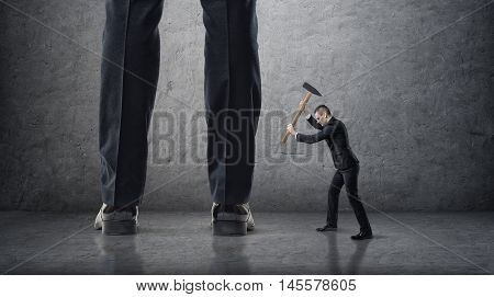 Small businessman hitting giant legs of another with hammer. Small business against big. Office confrontation. Disobedience.