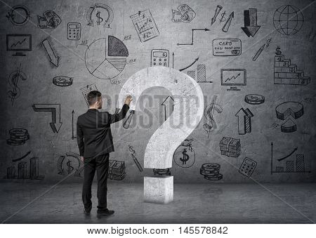 Back view of a businessman touching big 3d concrete question mark on the backround of concrete wall with business doodles. Questions and issues. Ideas and concepts. Solving problems.