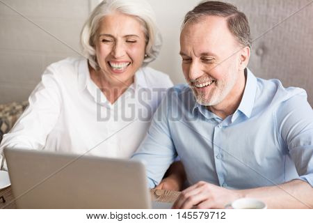 Express yourself. Cheerful delighted smiling couple sitting at the table and expressing gladness while using laptop
