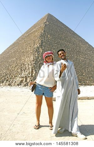 near the pyramids in Giza stands Caucasian woman and Arab man.Giza. September 2008