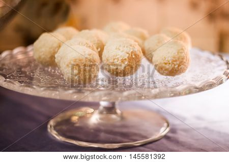 Cakes with coconut truffles in the evening light on a stand.