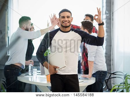 Picture of many business colleages or office workers showing victory of teamwork on background while handsome businessman posing with his hand in pocket in office interior.