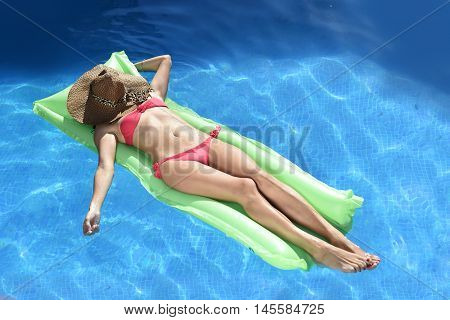 young beautiful woman in bikini and sun hat on face lying relax on float airbed at vacation hotel resort swimming pool in Summer enjoying holidays having sunbath with tan body