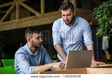 Picture of businessman listening to his colleague or partner concerning ner business system while working on laptop computer.