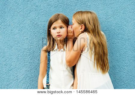 Two cute little girls sharing secrets, standing in front of blue wall at school backyard