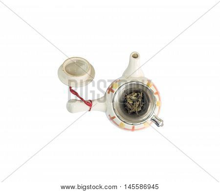 Closeup beautiful ceramic tea pot with dried tea leave isolated on with background in top view with clipping path