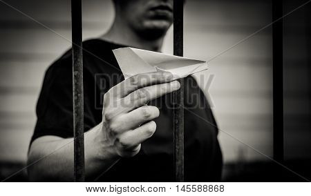 Teenager standing behind iron bars. In one hand he is holding a paper airplane.