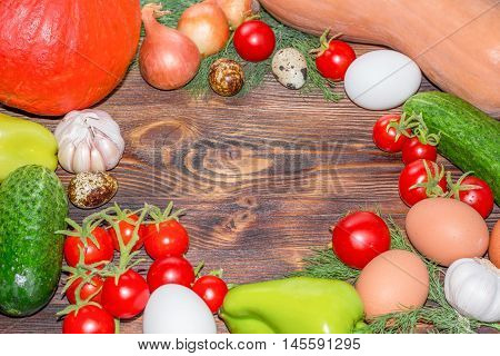 Bright Thanksgiving harvest composition of vegetables onions cucumbers peppers pumkin calabash tomatoes garlic eggs on dark wooden background