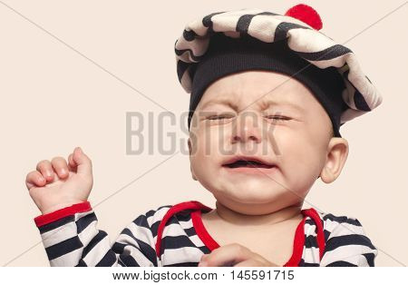 Cute baby boy crying raising his hands up. Little child in pain, suffering, teething, refusing and crying. Cute sad baby dressed nautical.