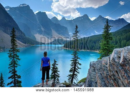Woman on cliff at Moraine Lake in Rocky Mountain. Banff National Park Alberta Canada.