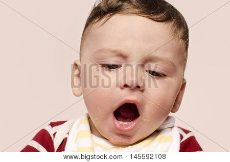Cute baby screaming refusing to eat baby food. Sad baby throwing a tantrum and yelling with his mouth open. Six month old beginning food diversification.
