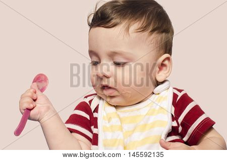 Child trying to feed himself baby food holding the spoon by himself. Six month old infant beginning food diversification.Cute baby boy wanting to eat food with the spoon.