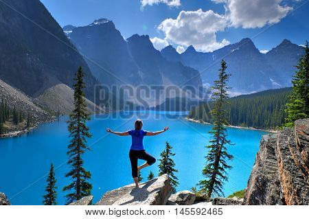 Woman in yoga pose meditating at Moraine Lake in Rocky Mountains. Banff National Park Alberta Canada.