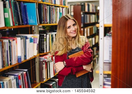 Smiling girl with a book between bookshelves in university library