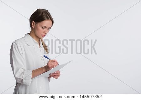 Beautiful nurse smiling and taking notes on a white isolated background.