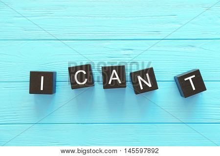 Black cubes with phrase I CANT on wooden background