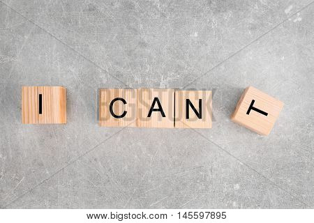 Wooden cubes with phrase I CANT on light background
