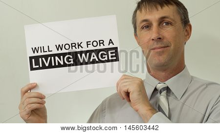 Middle aged man wearing a dress shirt and tie holds up a sign that says he will work for a living wage which refers to a wage that is high enough to maintain a normal standard of living.
