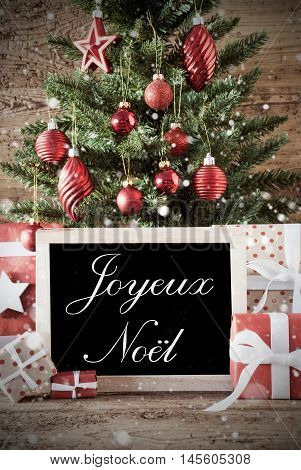 Nostalgic Christmas Card For Seasons Greetings. Christmas Tree With Balls. Gifts Or Presents In The Front Of Wooden Background. Chalkboard With French Text Joyeux Noel Means Merry Christmas