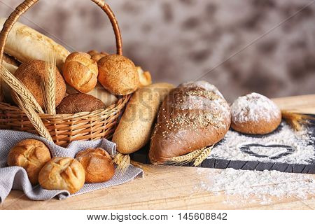 Lots of fresh bread in a basket and a board with flour on a wooden table