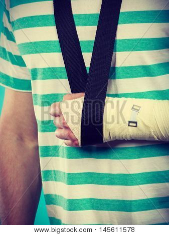 Fractures and dislocations concept. Part body male with hand in bandage. Helpful medication for painful arm of young man.