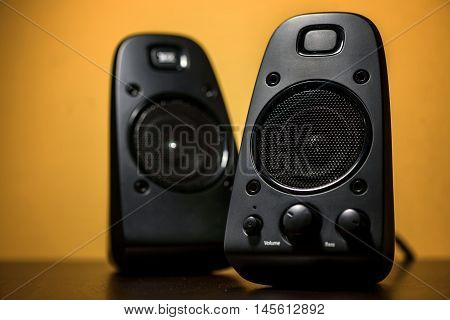Large Audio speakers on yellow background closeup